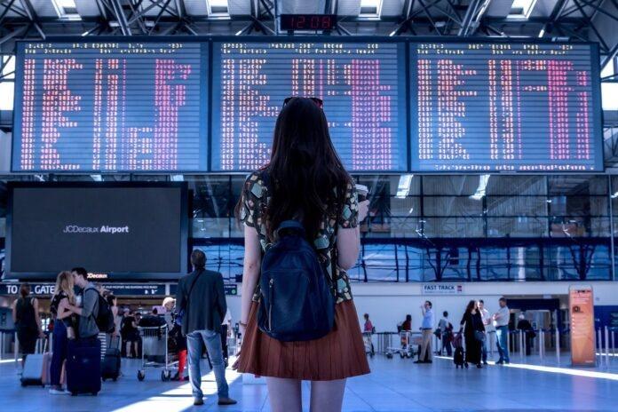 kobieta na lotnisku – tablica z rozkładem lotów
