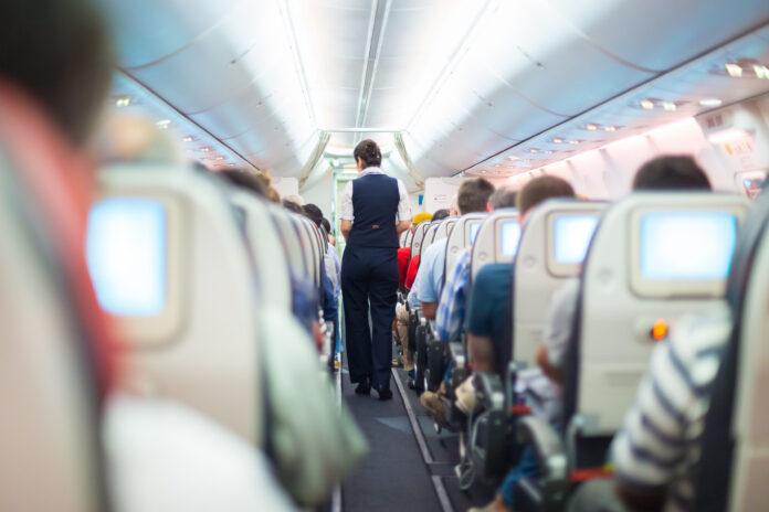 stewardessa idąca alejką między rzędami w samolocie