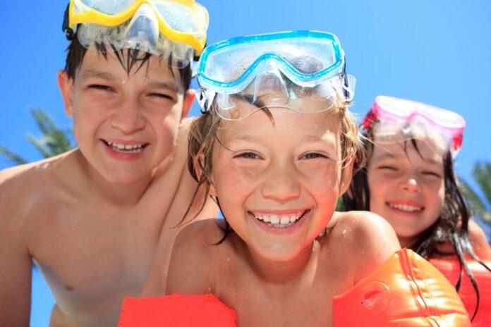 uśmiechnięte dzieci z maskami do pływania