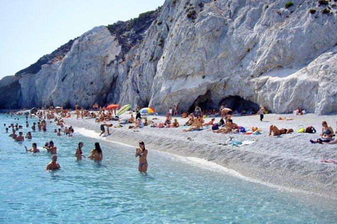 ludzie na białej kamienistej plaży otoczonej klifami