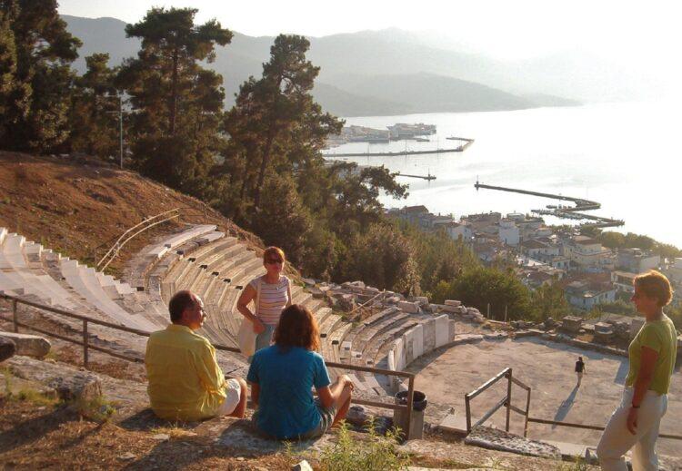 ludzie na terenie starożytnego teatru na wolnym powietrzu z widokiem na morze i miasteczko