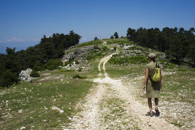 kobieta z plecakiem na szlaku wiodącym przez zielone wzgórze