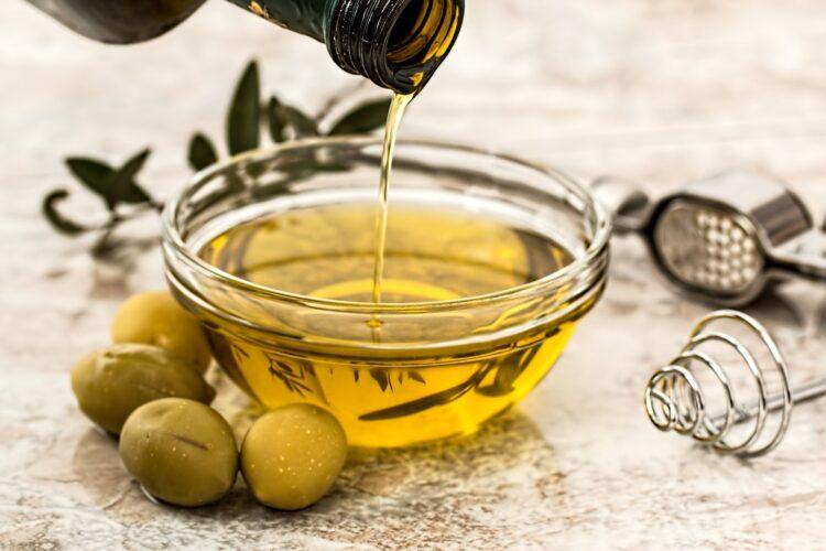 miseczka z oliwą obok oliwki i rozmaryn
