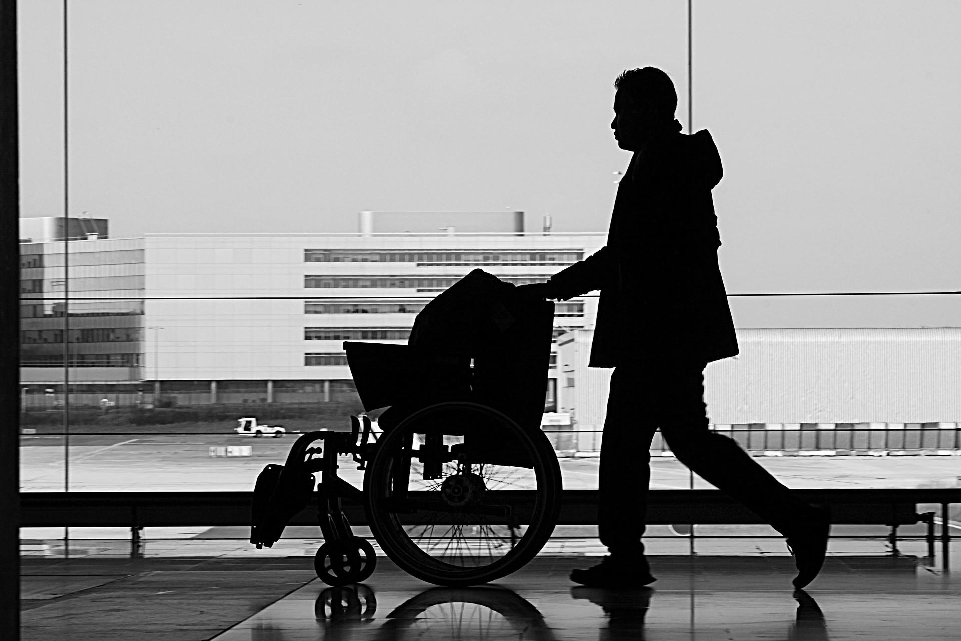 Mężczyzna idący z wózkiem inwalidzkim