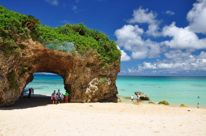 pokryty zielenią głaz z otworem, przez który przechodzą ludzie na plaży na tle lazurowego morza i niebieskiego nieba z chmurami