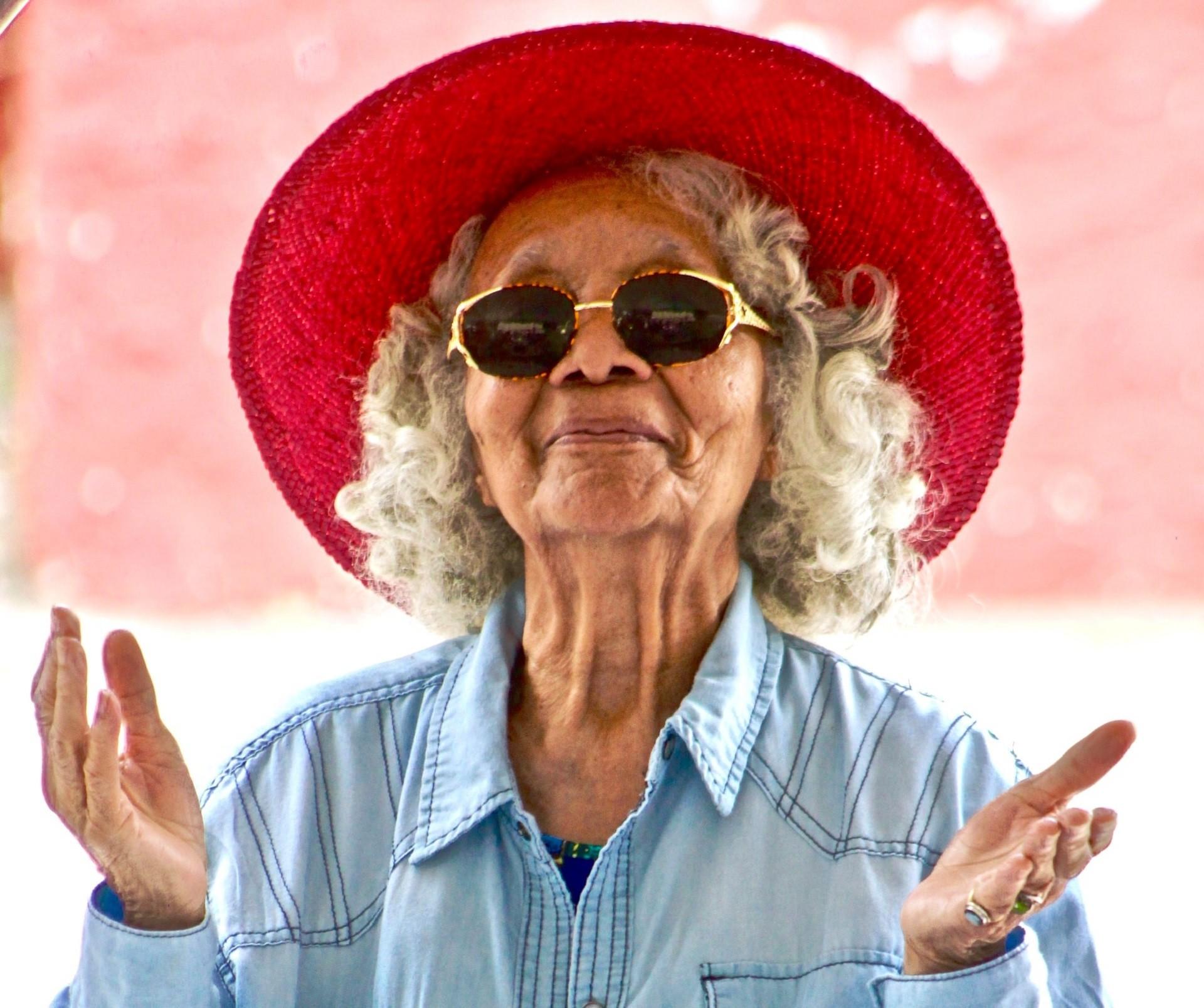 uśmiechnięta starsza kobieta w okularach przeciwsłonecznych i czerwonym kapeluszu z rondem rozkłada ręce