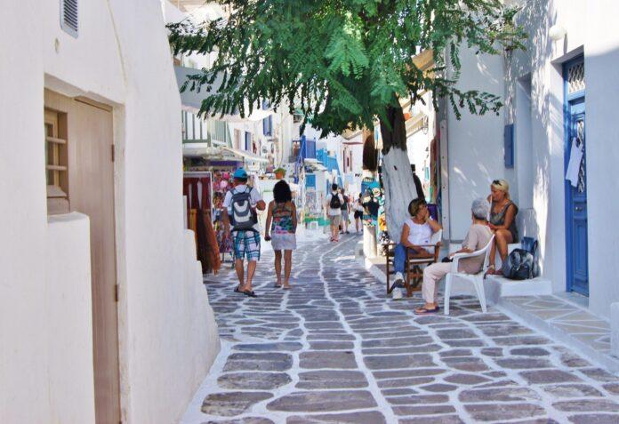 uliczka z kamiennymi płytami wzdłuż, której ciągną się pobielane domy z ludźmi na ulicy i drzewem