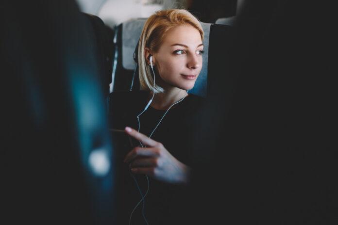 kobieta słucha muzyki na pokładzie samolotu