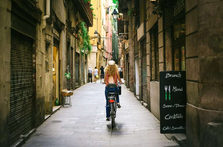 Woman-riding-bicycle-through-old-street-of-Barcelona-shutterstock_371095427