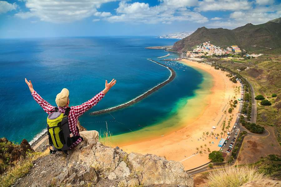 man-with-opened-arms-sitting-on-the-edge-of-a-cliff-enjoying-amazing-sea-view-of-the-beach-near-Santa-Cruz-de-Tenerife---Playa-de-Las-Teresitas-Canary-Islands-Spain-shutterstock_468796205