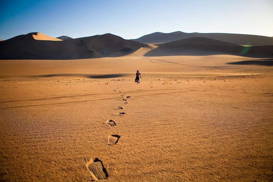 Libia-Walking-alone-in-the-desert-with-footsteps-shutterstock_569014618