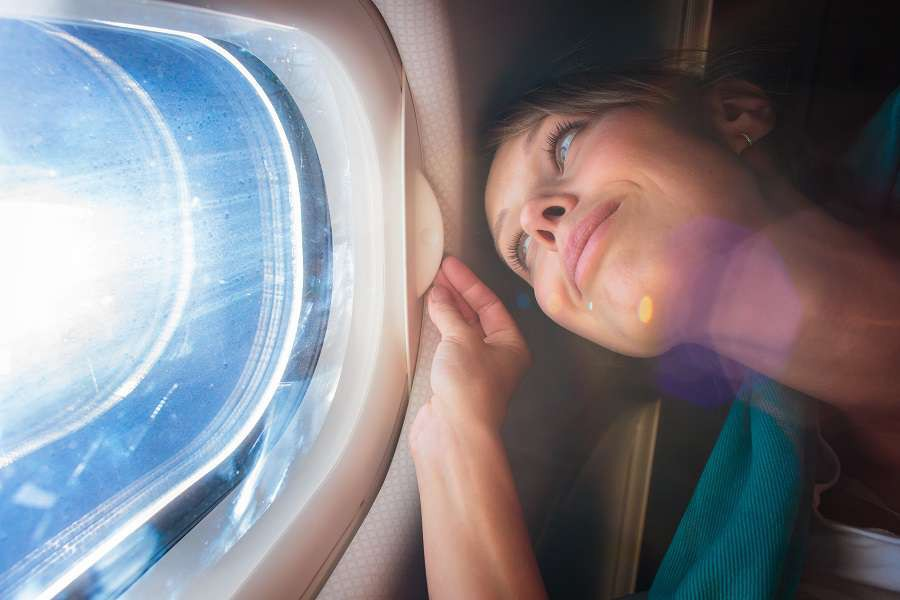 Happy-female-airplane-passanger-enjoying-the-view-from-the-cabin-window-over-the-blue-sky--shutterstock_235744918
