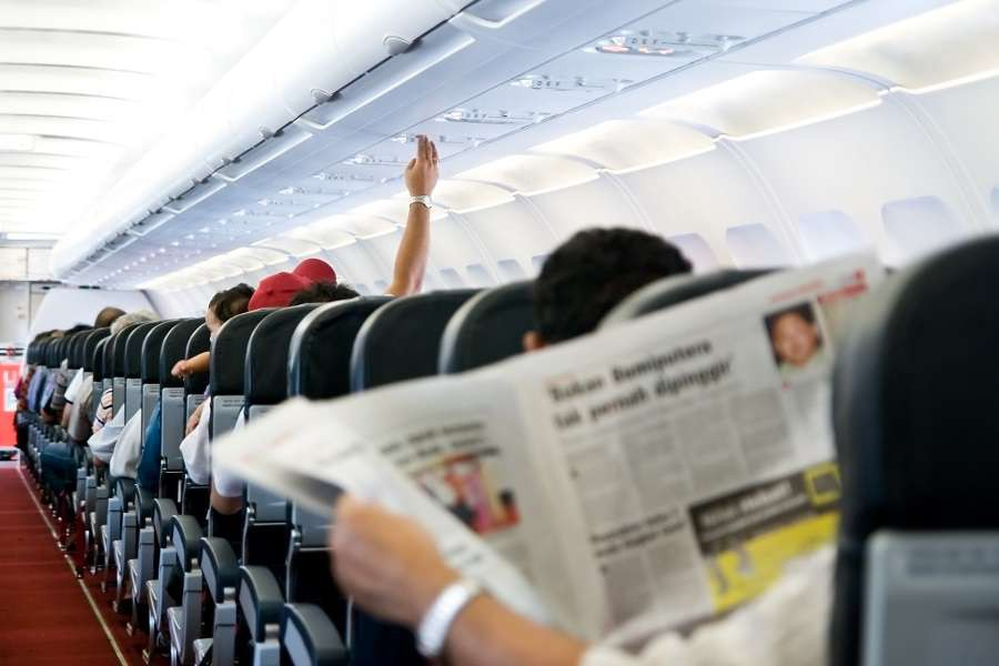 Reading-newspaper-in-a-plane-shutterstock_18487321-1