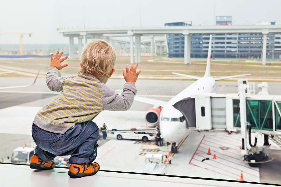 Little-baby-boy-waiting-boarding-to-flight-in-airport-transit-hall-and-looking-through-the-window-at-airplane-near-departure-gate.-shutterstock_316140362