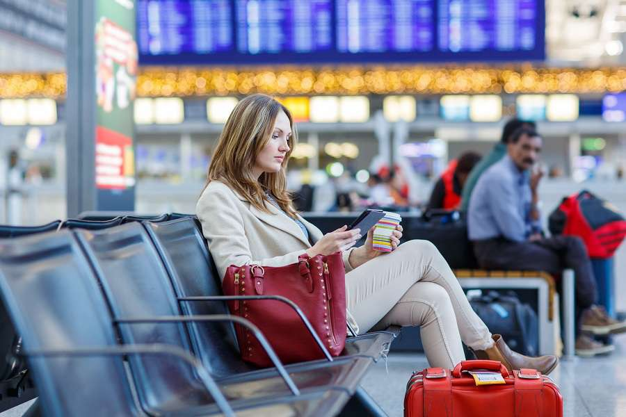 Young-woman-at-international-airport-reading-her-ebook-computer-and-drinking-coffee-to-go-while-waiting-for-her-flight.-Female-passenger-at-terminal-indoors.-shutterstock_245118346