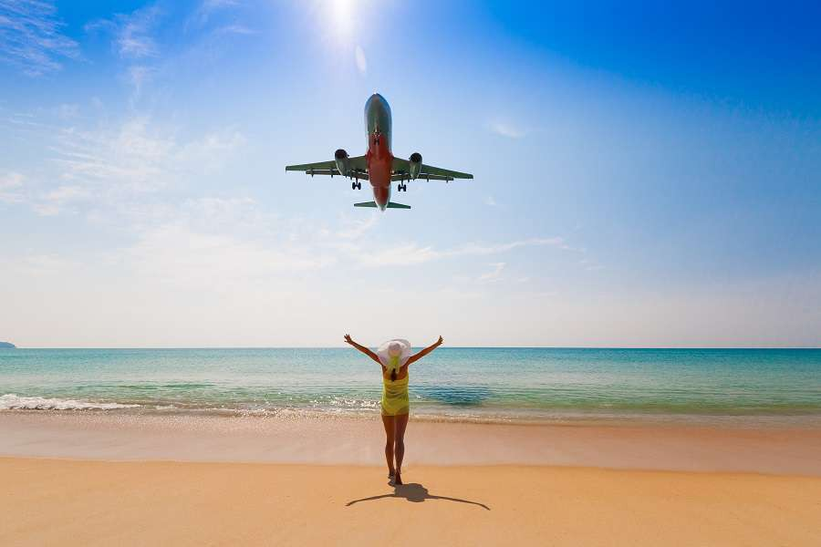 Beautiful-happy-fun-woman-and-flying-aircraft.-Tropical-blue-sun-sea.-Luxury-holiday-resort.-Island-Phuket-in-Thailand.-Impressive-paradise.-Hot-beach-Mai-Khao.--shutterstock_600954497