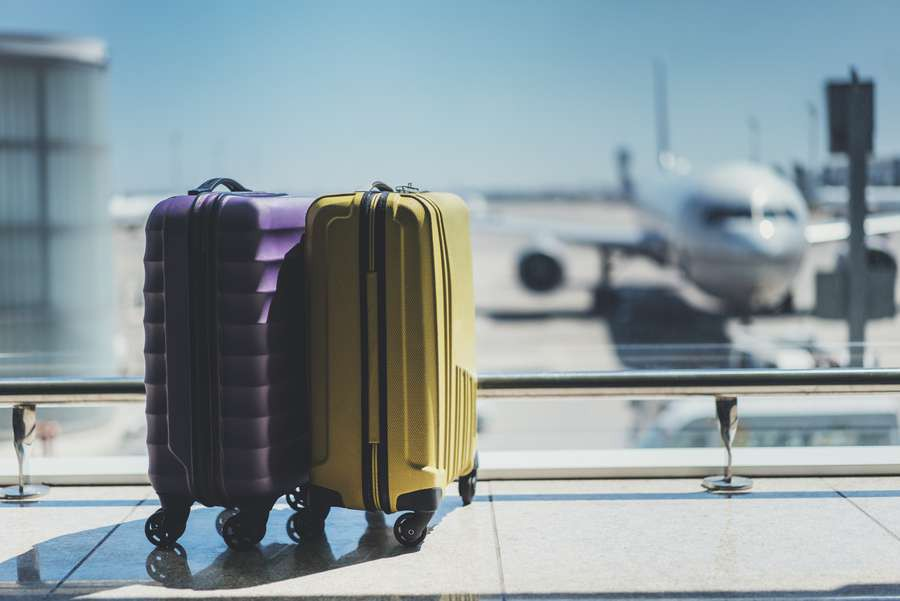 Suitcases-in-airport-departure-lounge-airplane-in-background-shutterstock_450980248