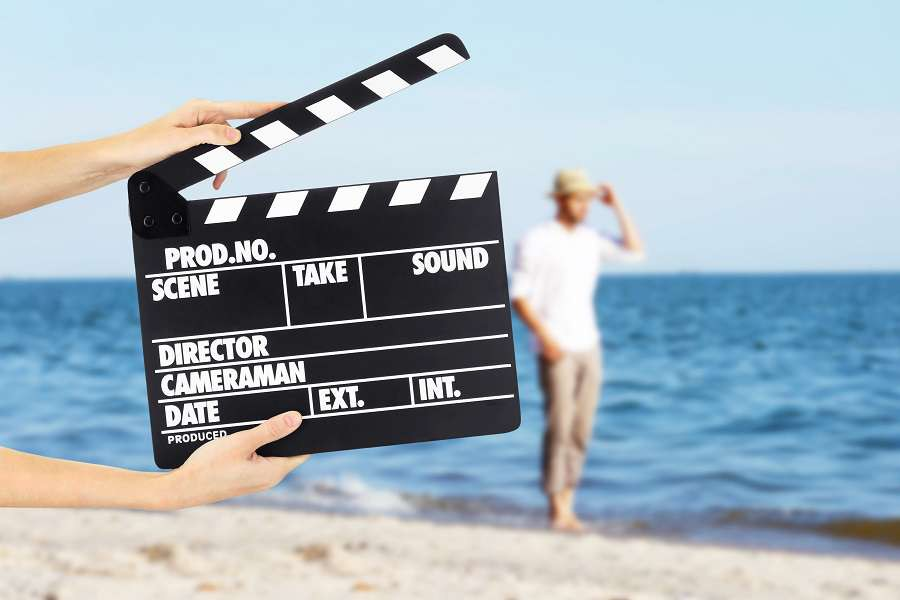 0.-Operator-holding-clapperboard-during-the-production-of-film-outdoor-shutterstock_381875335