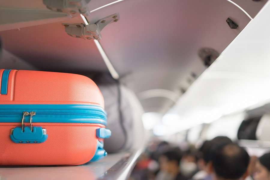 Carry-on-luggage-on-the-top-shelf-over-head-on-airplane-passenger-put-bag-cabin-compartment-air-craft-business-classvintage-colorcopy-space-shutterstock_599140022
