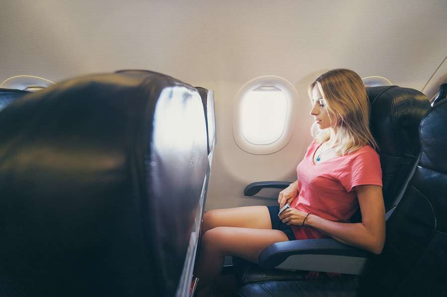 Safety-travel.-Young-woman-fasten-belts-while-sitting-in-airplane-seat-shutterstock_428320363