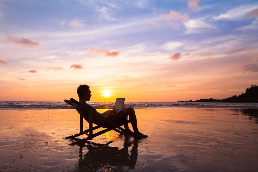 silhouette-of-happy-business-man-with-laptop-working-on-the-beach-shutterstock_377166919