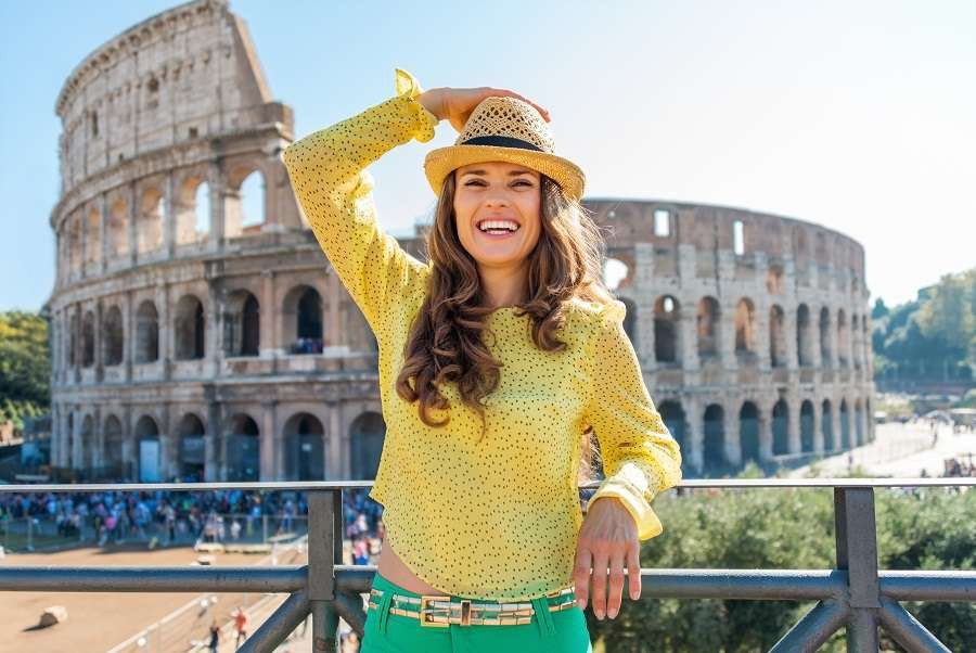 A-woman-tourist-is-standing-holding-her-hat-looking-into-the-distance-and-laughing.-She-is-delighted-to-be-in-Rome.-In-the-distance-the-Colosseum-and-tourists-on-a-hot-summers-day.shutterstock_280938689