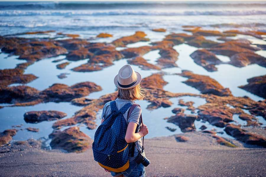 Tourism-and-photography.-Young-traveling-woman-with-camera-and-rucksack-walking-by-sea-beach-shutterstock_603946526