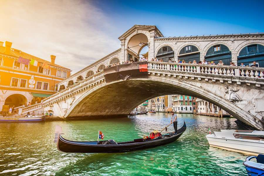 Beautiful-view-of-traditional-Gondola-on-famous-Canal-Grande-with-Rialto-Bridge-at-sunset-in-Venice-Wenecja-shutterstock_285467630