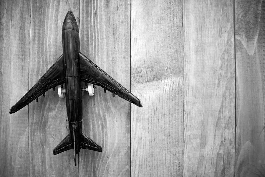 plane-on-wooden-background-top-view.-shutterstock_573373540