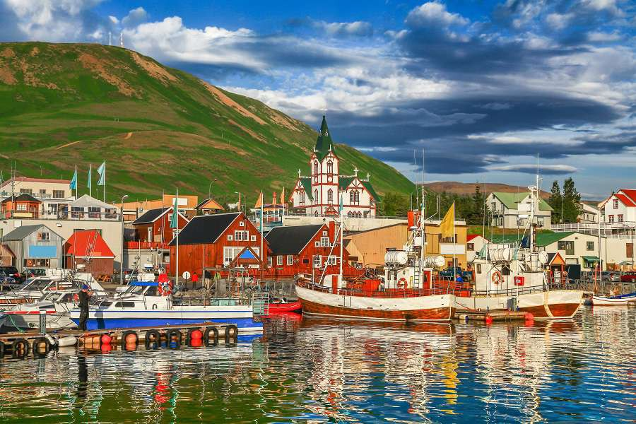 Beautiful-view-of-the-historic-town-of-Husavik-with-traditional-colorful-houses-and-traditional-fisherman-boats-lying-in-the-harbor-in-golden-evening-light-at-sunset-northern-coast-of-Iceland-shutterstock_32390