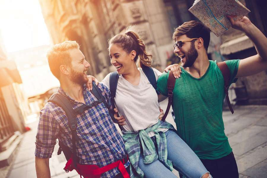 Happy-traveling-tourists-sightseeing-with-map-in-hand-shutterstock_501763291