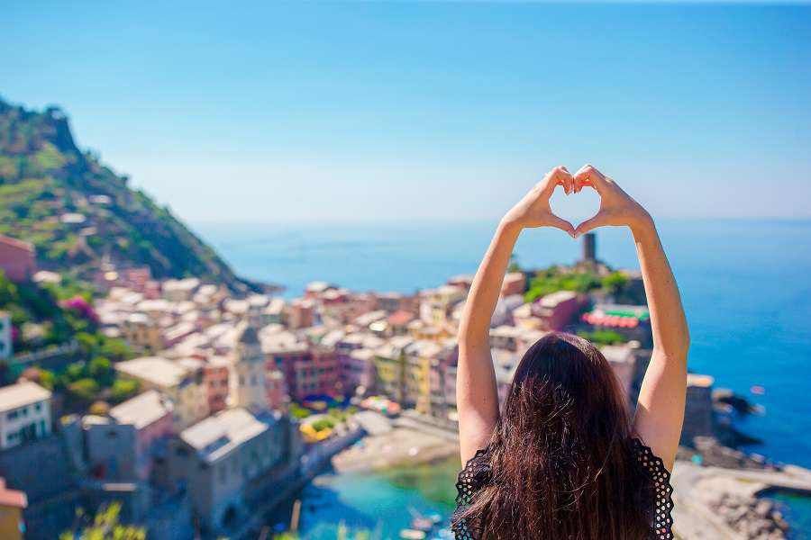 Young-beautiful-girl-making-with-hands-heart-shape-on-the-old-coastal-town-background-of-Vernazza-shutterstock_662627314