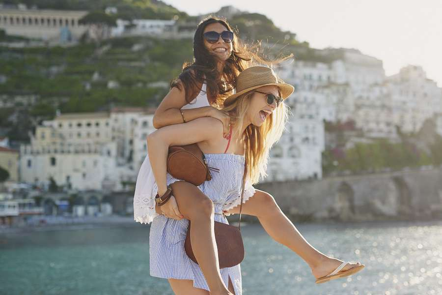 Piggyback-happy-tourist-friends-having-fun-on-summer-travel-adventure-vacation-laughing-shutterstock_586629710