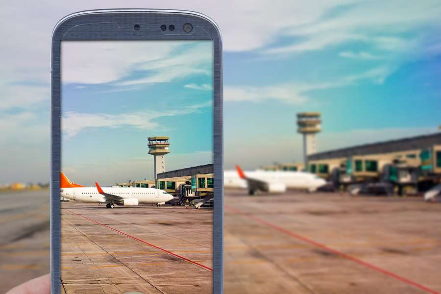 Smatrphone-and-airport-background.-Idea-of-taking-shots-accessing-apps-Internet-blogs-and-others.-The-blur-image-is-an-airport-scene-with-airplane-landed-and-another-taxing-for-taking-off.-shutterstock_2782072