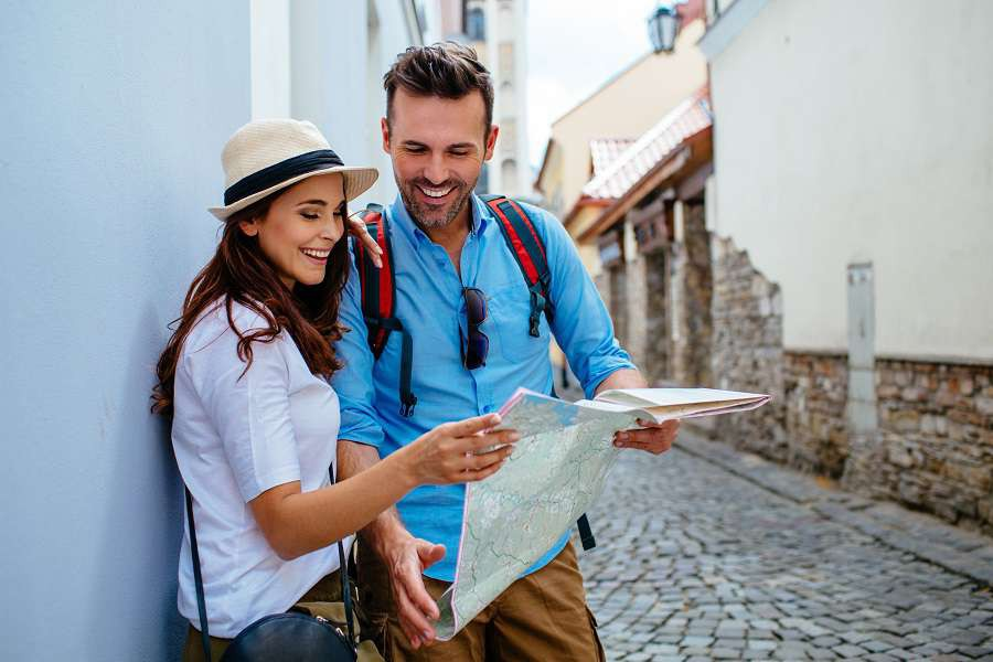 Happy-tourists-with-map-sightseeing-city-shutterstock_400245520