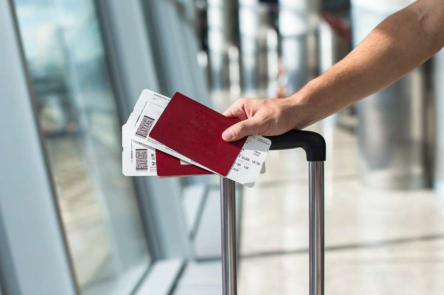 Closeup-of-man-holding-passports-and-boarding-pass-at-airport-shutterstock_210539380