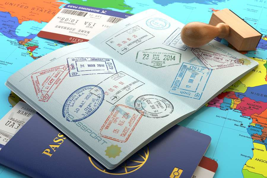 Opened-passport-with-visa-stamps-with-airline-boarding-pass-tickets-and-stamper-on-the-world-map.--shutterstock_397569799