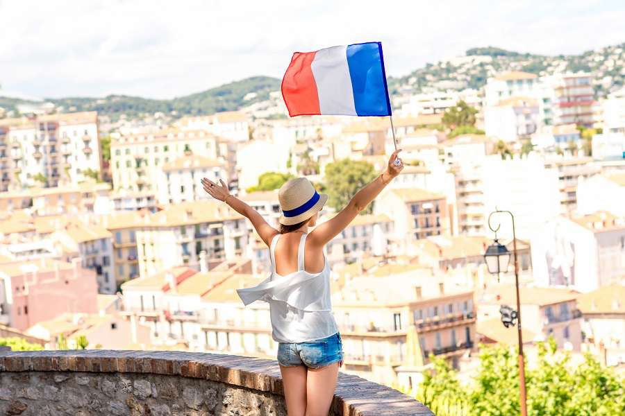 Young-female-traveler-with-flag-enjoying-great-view-on-french-riviera-in-Cannes-city-shutterstock_487000879