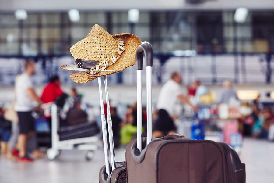 Airport-Luggage-with-straw-hat-at-the-airport-terminal-shutterstock_293900987-1