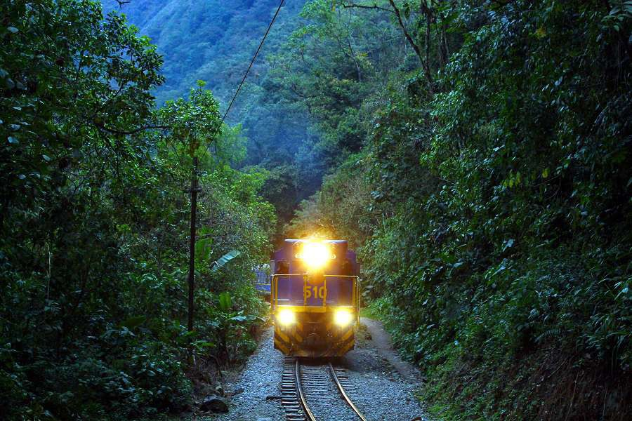 the-train-with-turned-on-head-lights-on-the-inca-track-train-rails-from-hydroelectrica-to-aguas-calientes-machu-picchu-in-peru-with-river-and-mountain-panorama-shutterstock_53595102