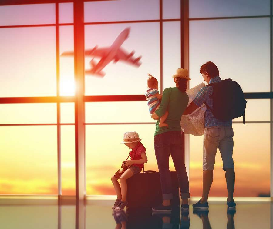 Happy-family-with-suitcases-in-the-airport.-shutterstock_400379911