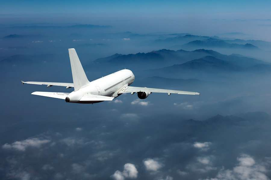 White-passenger-plane-in-the-blue-sky.-Aircraft-flies-high-over-the-clouds-and-foggy-mountain-landscape.-Airplane-view-back-and-top.-shutterstock_539220583