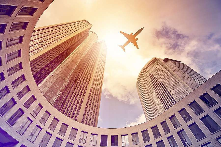 Frankfurt-plane-flying-over-modern-office-tower-in-the-sun-shutterstock_216614542