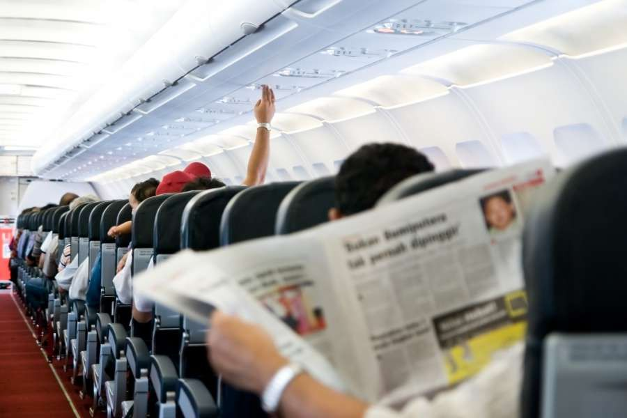 Reading-newspaper-in-a-plane-shutterstock_18487321